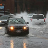MIKE SPRINGER/Staff photo<br /> Cars splash through flood waters at noon Friday on Rogers Street in Gloucester.<br /> 3/2/2018