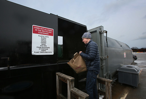 MIKE SPRINGER/Staff photo<br /> Peter Gove places a bag of recyclable items in a recycling bin on Friday at the Rockport Transfer Station.<br /> 3/9/2018