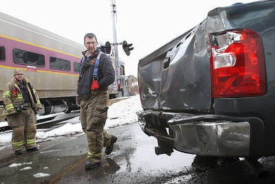 MIKE SPRINGER/Staff photo Gloucester fire captain Jamie Santos and firefighter Alison DeMuele, left, look at the damage to the back of a Chevrolet Silverado pickup truck that was hit Thursday by an MBTA commuter train at the intersection of Cedar and Willow streets in Gloucester. The woman who as driving the truck was uninjured. The train was delayed for 15 or 20 minutes while police investigated. There was no apparent damage to the train. 3/22/2018 [[MER1803221502045074]]