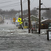 MIKE SPRINGER/Staff photo<br /> Flood waters stream across Route 133 in Essex at high tide Friday morning.<br /> 3/2/2018