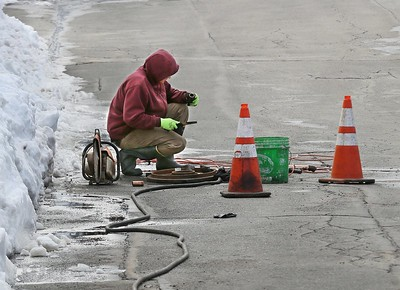 MIKE SPRINGER/Staff photo Tim Lodge of the Department of Public Works examines a piece of pipe while fixing a water line break Thursday on Whittemore Street in Gloucester. 3/15/2018 [[MER1803151537484068]]