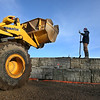 MIKE SPRINGER/Staff photo<br /> Oscar Miranda of the Manchester-based L.A.D. Company guides a front-loader filled with irregular stones, or riprap, into place Monday to be dumped next to a newly rebuilt seawall on Boardman Avenue in Manchester. The seawall was badly damaged during the weekend storm.<br /> 3/5/2018