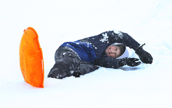 MIKE SPRINGER/Staff photo<br /> Twelve-year-old Stephen Martin wipes out while sledding Thursday at the Essex County Club in Manchester. Thursday was a snow day at Manchester Essex schools.<br /> 3/8/2018