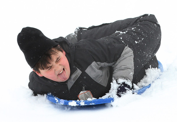 MIKE SPRINGER/Staff photo<br /> Ten-year-old Zac Carvalho goes down the hill on a sled Thursday at the Essex County Club in Manchester. Thursday was a snow day at Manchester Essex public schools.<br /> 3/8/2018
