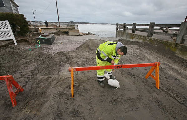 MIKE SPRINGER/Staff photo<br /> Jonathan Church of the Gloucester Department of Public Works ties a sandbag to a sawhorse Monday to block vehicles from approaching the entrance to Long Beach, near the Cape Ann Motor Inn, where everal feet of sand were completely washed away during the weekend's storm.<br /> 3/5/2018