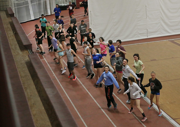 MIKE SPRINGER/Staff photo<br /> Runners do a warm-up exercise on the first day of track practice Monday in the field house at Gloucester High School.<br /> 3/19/2018