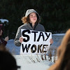 MIKE SPRINGER/staff photo<br /> A student holds a sign calling for people to stay politically awakened during an anti-gun violence walkout Thursday at Gloucester High School.<br /> 3/15/2018
