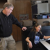 MIKE SPRINGER/Staff photo<br /> Composer-in-residence G. Paul Naeger of Ipswich looks on as fifth-grader Aby Amigo explains her composition to him Friday in Rich Carpenter's music class at Essex Elementary School. Naeger has been visiting the school two days a week to teach the fundamentals of music composition.<br /> 3/9/2018