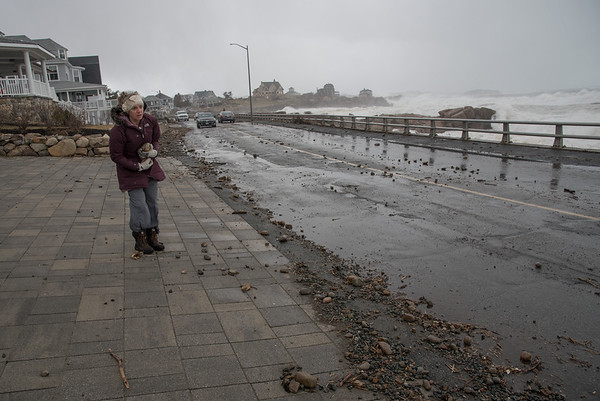 Desi Smith Photo.   A Atlantic Rd home owner, gathers rocks from her driveway and throws them back into the ocean during Saturday afternoon's storm.   March 3,2018