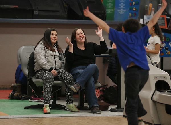 MIKE SPRINGER/Staff photo<br /> Brenda Dirusso of Gloucester celebrates with her daughter Ava, 9, after her son Zach, 8, made a successful roll Saturday while candlepin bowling at the Cape Ann Lanes in Gloucester.<br /> 3/17/2018