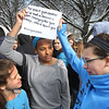 "MIKE SPRINGER/Staff photo<br /> Seventh graders Jada Exama, center, and Sabine Harnisch hold a sign as their classmate Natalie Lamond, left, visits with them during a student walkout Wednesday at Rockport High School and middle school to protest U.S. gun policy on the one-month anniversity of the February 14 mass shooting at Marjory Stoneman Douglas High School in Parkland, Florida. Exama's and Harnisch's sign said ""The most gun control we've had in America is Apple changing the gun emoji, into a squirt gun.""<br /> 3/14/2018"