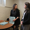 MIKE SPRINGER/Staff photo<br /> Sayonara Reyes, left, manager of the Parent Information Center, discusses a stack of transfer applications with intake clerk Vanessa Fegundes on Thursday in Reyes' office at Collins Middle School.<br /> 3/1/2018<br /> 3/1/2018