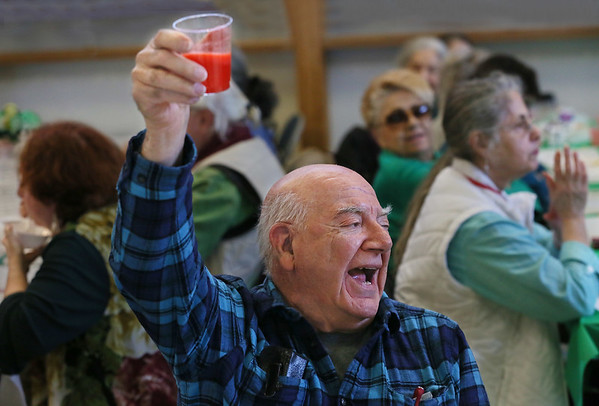 MIKE SPRINGER/Staff photo<br /> Sam Garrisi raises his drink in salute Thursday during the St. Patrick's Day luncheon at the Rose Baker Senior Center in Gloucester. In addition to the musical sing-along, guests enjoyed a traditional Irish dinner of corned beef and cabbage. St. Patrick's Day will be on Saturday, March 17.<br /> 3/15/2018