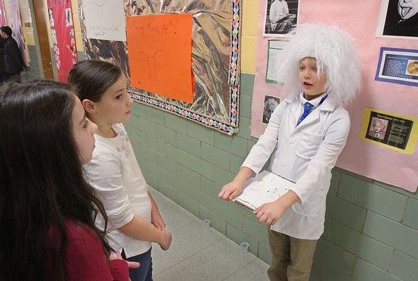 "MIKE SPRINGER/Staff photo<br /> Fifth-grader Zachary Lacey portrays physicist Albert Einstein as third-graders Liliana Figueiredo, left, and Malia Bolcome look on Friday during a ""Wax Museum"" event Veterans Elementary School in Gloucester. The entire fifth grade class participated in the program, which was visited by parents and students from other grades.  The fifth-graders dressed as famous historical figures and stood still, like wax statues, until a visitor pushed a button. They would then spring into life and recite a first-person account of the famous person's life.<br /> 3/23/2018"