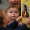 MIKE SPRINGER/Staff photo<br /> Eight-month-old Sage Shover looks up at the storyteller during a musical storytime Friday at the Sawyer Free Library in Gloucester. The program was led by actress Ruthanne Paulson of Gloucester.<br /> 3/16/2018