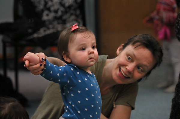 MIKE SPRINGER/Staff photo<br /> Liz Brown and her 10-month-old daughter Mavis follow along during a musical storytime Friday at the Sawyer Free Library in Gloucester.<br /> 3/16/2018