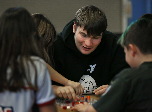 MIKE SPRINGER/Staff photo<br /> Group leader Brian Amero plays a board game with students during the Cape Ann YMCA's after-school program at East Gloucester Elementary School.<br /> 1/19/2018