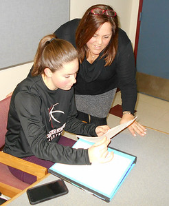 """SEAN HORGAN/Staff photo/Gloucester High School junior Liz Schuster, left, works with teacher Rachel Rex on the """"Areas Vulnerable to Storm Surges and Sea Level Rise"""" project focused on Gloucester. The 70 students who worked on the project will present their findings to the public Friday."""
