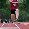 DAVID LE/Staff photo. Gloucester sophomore Kaitlin Marques leaps high in the air as she flies towards the sand pit during the long jump against Marblehead. 5/24/16.