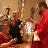 Gloucester: At the Annual Crowning Feast of the Holy Spirit held at Our Lady of Good Voyage Parish on Sun., May 15, 2016. Bart and Mary Piscitello were honored this year with the Crown and they and their family were crowned first at the end of the Mass.  Father Jim Achadinha, right, is assisted by Mark Davis and David Rose, not shown, during the ceremony. Photo by Allegra Boverman