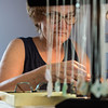 Desi Smith/Staff photo.  Loie Levine of Be-Lo The Sea Treasures Jewelry, works on making a pair earrings from local seaglass, during a demonstration held at Premier Imprints on Main Street Saturday afternoon, as part of the Harbortown Arts Festival .  May 28,2016