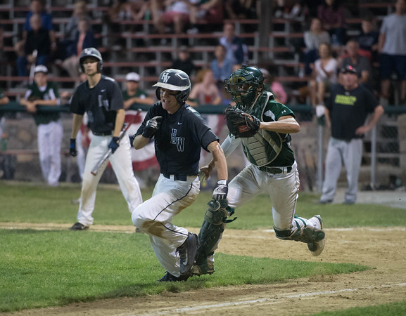 Desi Smith/Staff photo.       Manchester Essex's catcher Robbie Sarmanian (8) chases down Hamilton-Wenham's Harrison O'Brien (8) caught going home on a past ball at home plate during the Cape Ann Savings Bank Memorial Day Baseball Classic Tournament Finals held Saturday night at Evans Field in Rockport. The Hornets lost 3-2