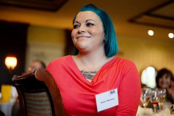 PAUL BILODEAU/Staff photo. Kylee Moriarty, a recovering heroin addict, smiles broadly as Gloucester Chief Leonard Campanello holds her up as one of the examples of the Angel Program during the Anti-Defamation League's annual Essex County Law and Education Day Event at the Kernwood Country Club in Salem