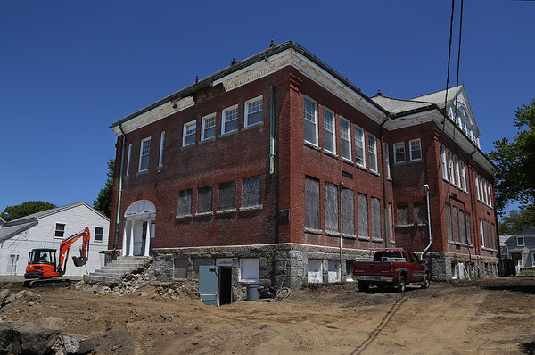 MIKE SPRINGER/Staff photo<br /> A worker uses a back hoe, at far left, to clear stones Wednesday on the Acacia Street side of the old Maplewood School in Gloucester.<br /> 5/23/2018
