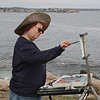 MIKE SPRINGER/Staff photo<br /> Ann Goldberg of Revere paints from the rocks on Gloucester's Back Shore with a group of members of the North Shore Arts Association.
