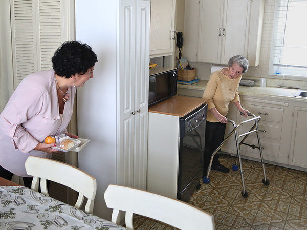 MIKE SPRINGER/Staff photo<br /> SeniorCare nutrition director Paula Curley, left, looks around the corner to see her aunt Rose Demitri, 95, while delivering her Meals On Wheels lunch Tuesday in Gloucester. Curley joined Gloucester Mayor Sefatia Romeo Theken in visiting the homes of eight Meal On Wheels recipients over the age of 90. <br /> 5/8/2018
