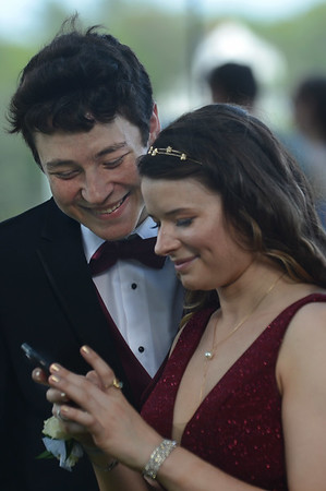 MIKE SPRINGER/Staff photo<br /> Jameson Kamm and Grace Porter look at a photo on her phone Friday evening at Tuck's Point in Manchester before heading off to the Manchester Essex Regional High School prom.<br /> 5/25/2018