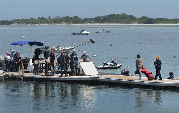 "MIKE SPRINGER/Staff photo<br /> The crew of a German television movie, ""Second Spring,"" films a scene Thursday on the dock at Conomo Point. In the scene, a young woman played by German actress Catherine Bode, second from right, arrives on an island to discover she has been swindled out of her money and has no house to stay in. The police officer at far right is played by Petra Kleinert.<br /> 5/31/2018"