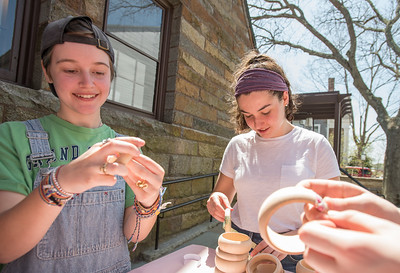 AMANDA SABGA/Staff photo  From left, Elene Karlberg, 15, and Abby Conway, 15, make bracelets as Mother's Day gifts at the Manchester Public Library.   5/2/18