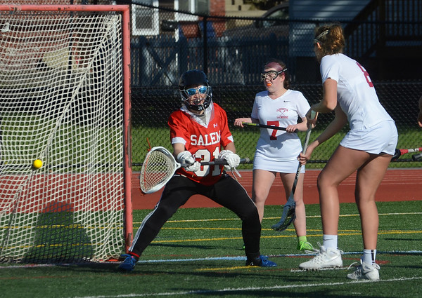 MIKE SPRINGER/Staff photo<br /> Gloucester's Sophie Caldwell, right, shoots the ball past Salem goaltender Hannah Valenzuela as Gloucester's Jesse Alexander, center, looks on during varsity lacrosse action Monday in Gloucester.<br /> 5/21/2018