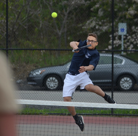 MIKE SPRINGER/Staff photo<br /> Peabody's Max Leete jumps up to hit a high forehand during varsity tennis doubles play Wednesday at Gloucester.<br /> 5/16/2018
