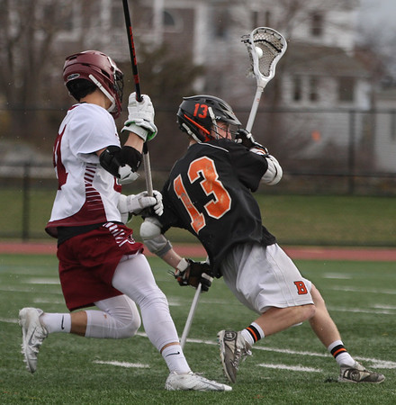 MIKE SPRINGER/Staff photo<br /> Beverly's John Wholley, right, is pursued by James Nelson of Gloucester during varsity lacrosse play Monday in Gloucester.<br /> 4/30/2018