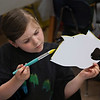 "MIKE SPRINGER/Staff photo<br /> Second-grader Mackenzie Robertson concentrates on her work Friday during ""Fish Painting Day"" at East Gloucester Elementary School. Students from every grade each painted a fish under the guidance of artist-in-residence Loren Doucette. Each class was assigned its own color of the rainbow (second grade's was yellow) and the fish will be hung from the ceiling for parents to see on Portfolio Night in June.<br /> 5/11/2018"