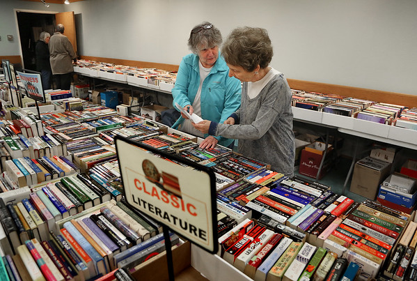 MIKE SPRINGER/Staff photo<br /> Friends of The Sawyer Free Library members, from left, Carol Kelly and Gail Sarofeen confer Wednesday while preparing for the club's annual book sale. The sale, which benefits the club's activities in support of the library, will feature over 1,000 books --both fiction and non-fiction -- in good condions on a variety of topics. It will also include audio books, DVDs, CDs and magazines. The sale opens for members of the Friends of the Sawyer Free Library on Thursday from 3 to 7 p.m. People are welcome to join the organization at the door. The sale then continues for the general public on Friday from 9 a.m. to 4 p.m. and Saturday from 9 a.m. to 2 p.m.<br /> 5/16/2018