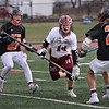 MIKE SPRINGER/Staff photo<br /> Gloucester's Jacob Enos carries the ball between Matthew Rawding, left, and Clark Marchand of Beverly during varsity lacrosse play Monday in Gloucester.<br /> 4/30/2018