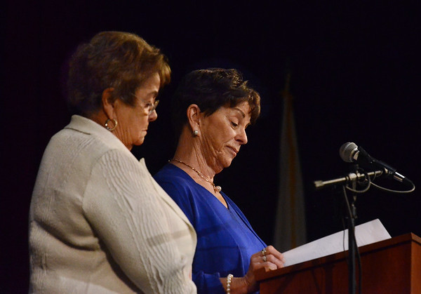 MIKE SPRINGER/Staff photo<br /> Sisters Eileen Greely Pereira, left, and Judith Greely Bove read the last letter their mother received from their father, Ralph John Greeley, a U.S. Marine who died in 1945 during the Battle for Sugar Loaf Hill in Okinawa during World War II, during a Memorial Day ceremony Monday at Gloucester High School.<br /> 5/28/2018