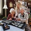 MIKE SPRINGER/Staff photo<br /> U.S. Navy veteran Robert McKinnon, 93, looks through an album with photos from his time serving in World War II with his wife Virginia Frontiero McKinnon, 88, and daughter Mary-Ellen McKinnon Burnham.<br /> 5/23/2018