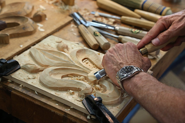 MIKE SPRINGER/Staff photo<br /> Dave Cutherell of Austin, Texas, uses a chisel to make a relief carving of a fleur-de-lis during David Calvo's wood-carving workshop in Gloucester.<br /> 5/28/2018