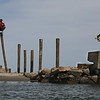 MIKE SPRINGER/Staff photo<br /> Workers drive new pilings into the sand Friday afternoon in the first phase of repairing the storm-damaged footbridge at Good Harbor Beach in Gloucester. The Department of Public Works expects to begin work on the planking on Monday.<br /> 5/18/2018