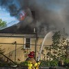 Desi Smith Photo.     Capt. Phil Harvey attacks flames as they rip through the roof at 1 Babson Ct from the back yard on Hampton St Sunday afternoon, as the crew works the front from Babson Ct off Western Ave.       May 13, 2018 [[MER1805131929252232]]
