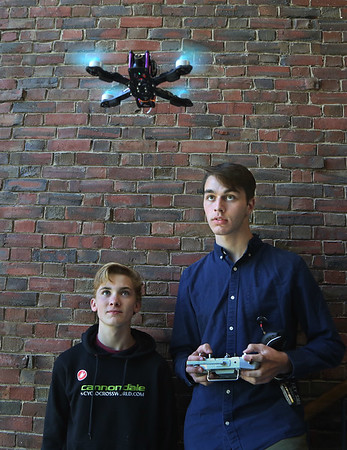 MIKE SPRINGER/Staff photo<br /> Austin Monell, left, and Aiden Cunha, both juniors, watch as Cunha uses a remote control console Wednesday to fly a drone in a stairwell at Gloucester High School. The students are involved in various advanced projects in the school's engineering program.<br /> 5/9/2018