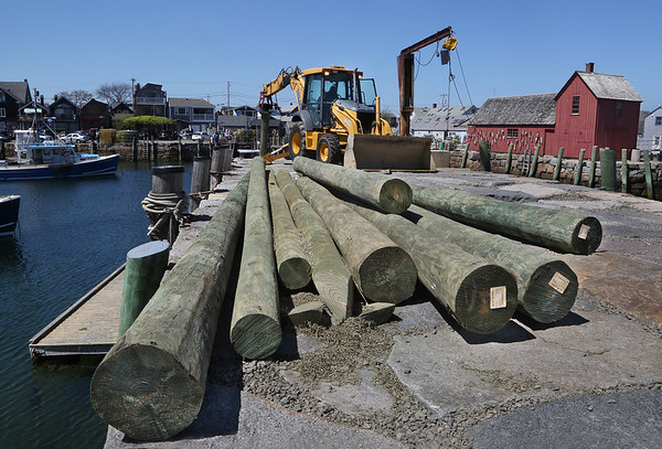 MIKE SPRINGER/Staff photo<br /> Workers drive a new piling into the floor of Rockport Harbor as others lay waiting Monday on the T-Wharf.<br /> 5/14/2018