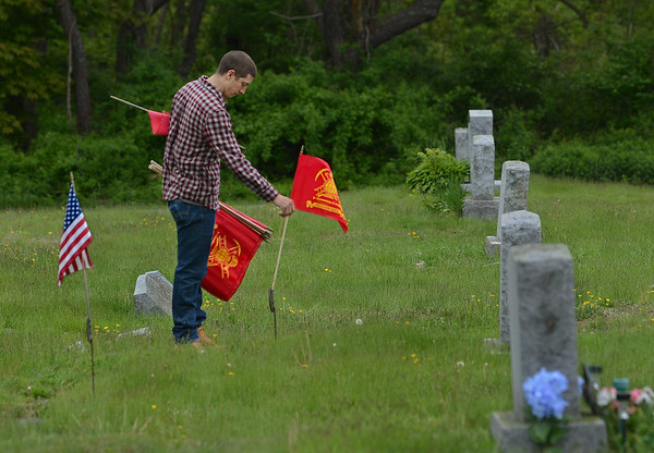 MIKE SPRINGER/Staff photo<br /> Gloucester firefighter Nick Aiello places a firefighter memorial flag on a grave Tuesday at Beechbrook Cemetery in Gloucester. A group of about 10 firefighters spent the day placing more than 100 flags on the graves of firefighters in cemeteries across Gloucester, Rockport and Essex in preparation for Memorial Day.<br /> 5/22/2018