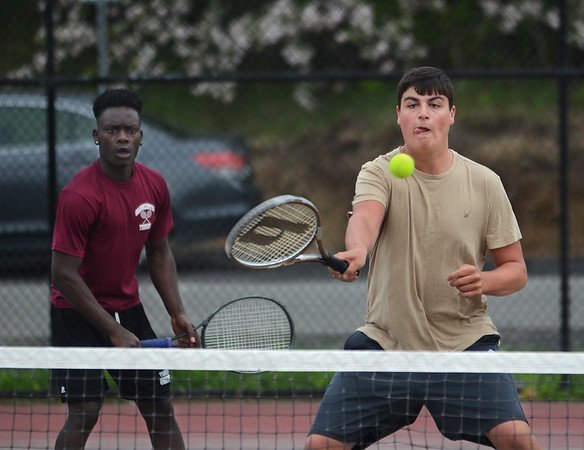 MIKE SPRINGER/Staff photo<br /> Glouceater's Ryan Muniz hits a volley at the net as his doubles partner Joe Kibango looks on Wednesday during varsity tennis play against Peabody in Gloucester.<br /> 5/16/2018