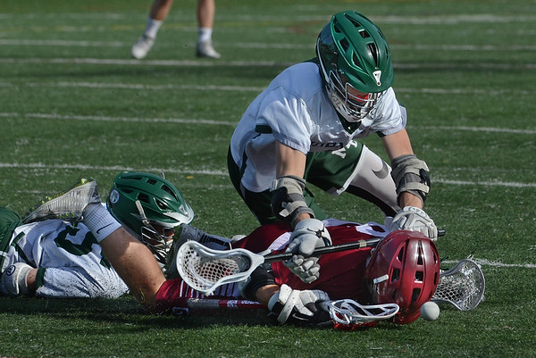 MIKE SPRINGER/Staff photo<br /> Gloucester's Ryan Argentino falls face-first into the ground as Chris Brosch, left, and Jake Anthanas of Manchester Essex scuffle with him for the ball during varsity lacrosse action Friday in Manchester.<br /> 5/18/2018