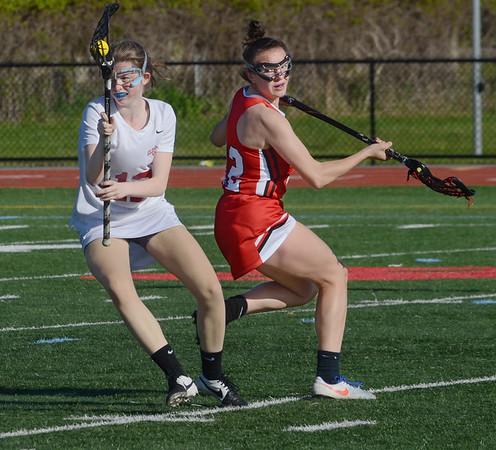 MIKE SPRINGER/Staff photo<br /> Gloucester's Caroline Muniz, left, turns away from a Salem player during varsity lacrosse action Monday in Gloucester.<br /> 5/21/2018